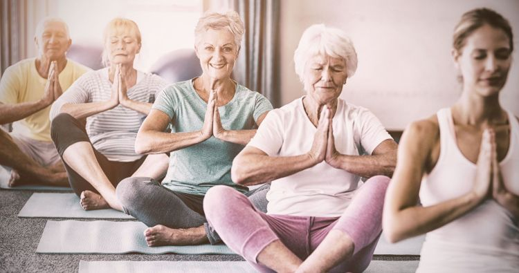 70189886 - instructor performing yoga with seniors during sports class
